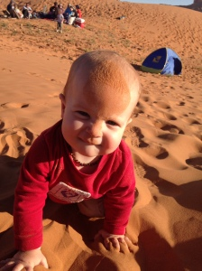 Baby born in the desert loves the sand